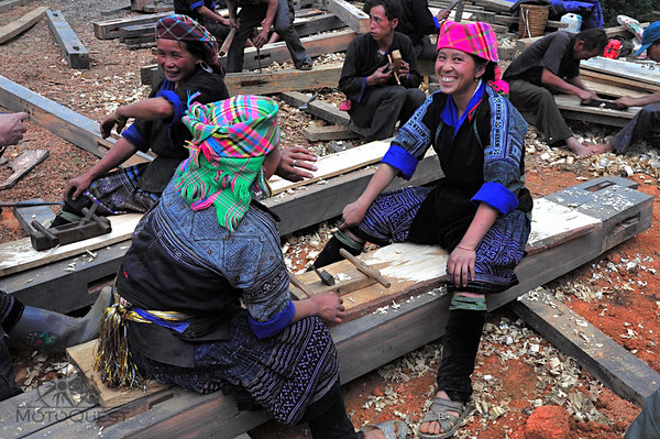 Hmong girls plaining wood to be used for house siding
